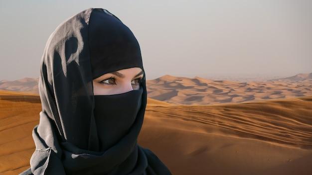 Porträt der schönen islamischen frau im hijab auf wüstenhintergrund.