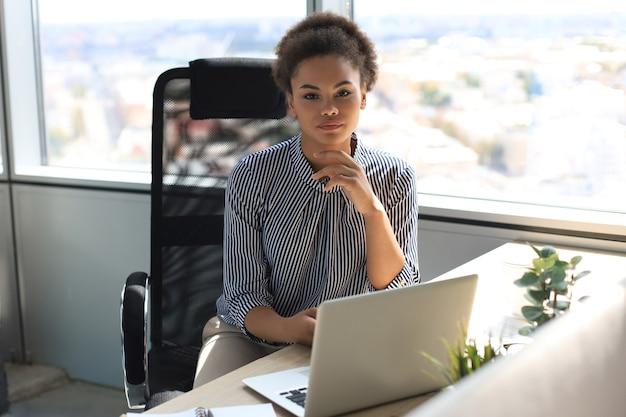 Porträt der schönen jungen afroamerikanerfrau, die mit laptop beim sitzen am tisch arbeitet.