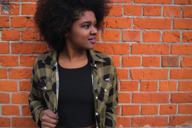 Porträt der schönen jungen afroamerikanischen lateinamerikanischen frau mit dem lockigen haar, das gegen backsteinmauer steht.
