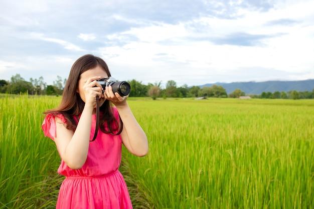 Porträt der schönen jungen asiatin im weinleserosakleid, das ein foto macht