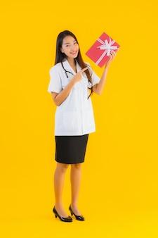 Porträt der schönen jungen asiatischen ärztin, die rote geschenkbox zeigt
