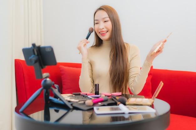 Porträt der schönen jungen asiatischen frau bewertungen und verwendet kosmetik auf dem sofa