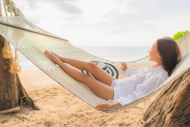 Porträt der schönen jungen asiatischen frau, die auf hängematte um strand im urlaub entspannt