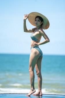 Porträt der schönen jungen asiatischen frau, die bikini am strand trägt