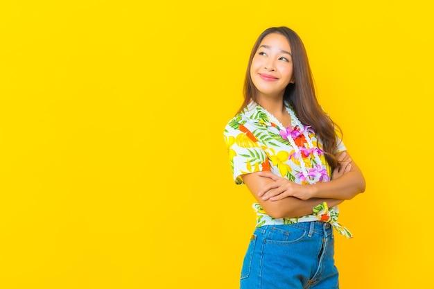 Porträt der schönen jungen asiatischen frau, die buntes hemd auf gelber wand trägt