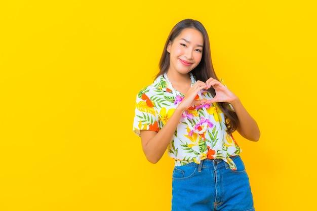 Porträt der schönen jungen asiatischen frau, die buntes hemd trägt und herzzeichen auf gelber wand macht