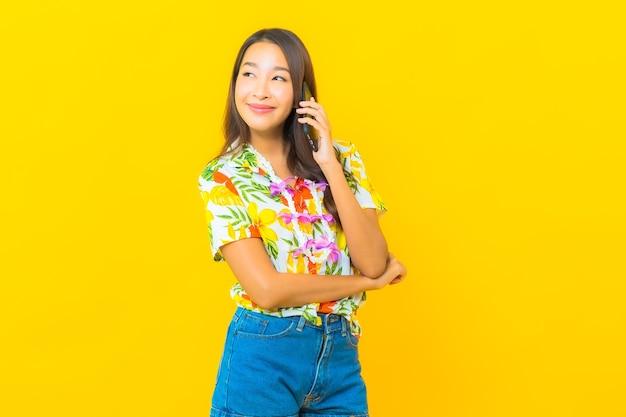Porträt der schönen jungen asiatischen frau, die buntes hemd unter verwendung des intelligenten handys auf gelber wand trägt
