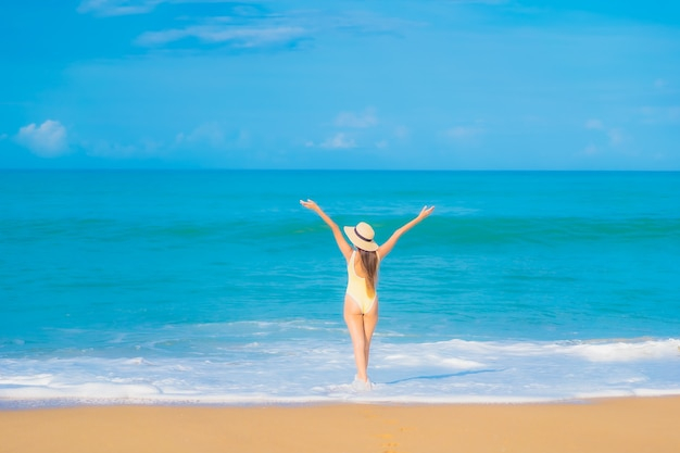 Porträt der schönen jungen asiatischen frau, die im strand im reiseurlaub entspannt