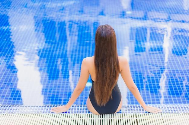 Porträt der schönen jungen asiatischen frau, die sich um den außenpool im hotelresort entspannt