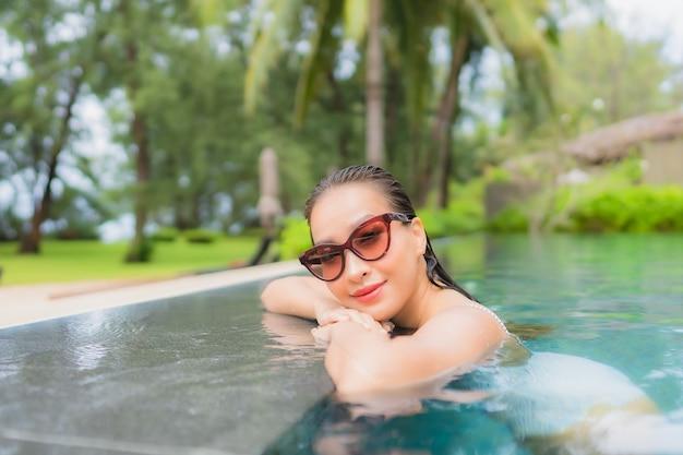 Porträt der schönen jungen asiatischen frau, die sich um den außenpool im hotelresort fast meer entspannt