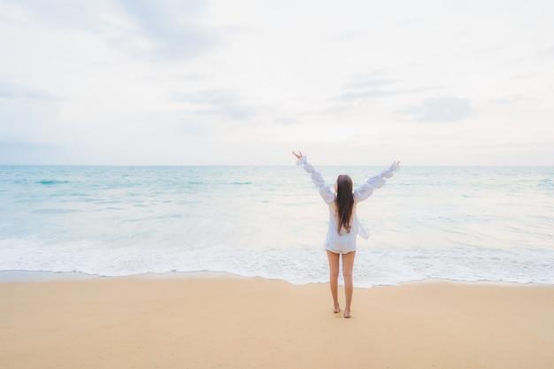 Porträt der schönen jungen asiatischen frau, die sich um strand im freien im reiseurlaub entspannt