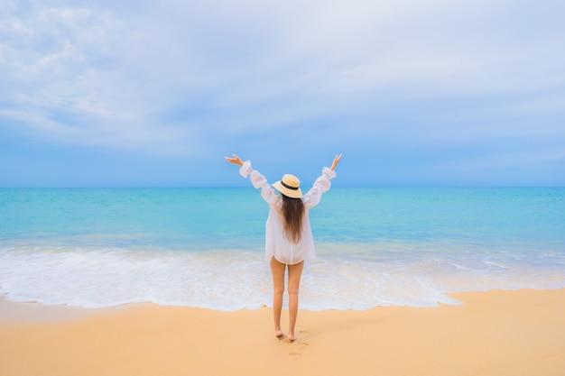 Porträt der schönen jungen asiatischen frau, die sich um strandmeerozean im reiseurlaub entspannt