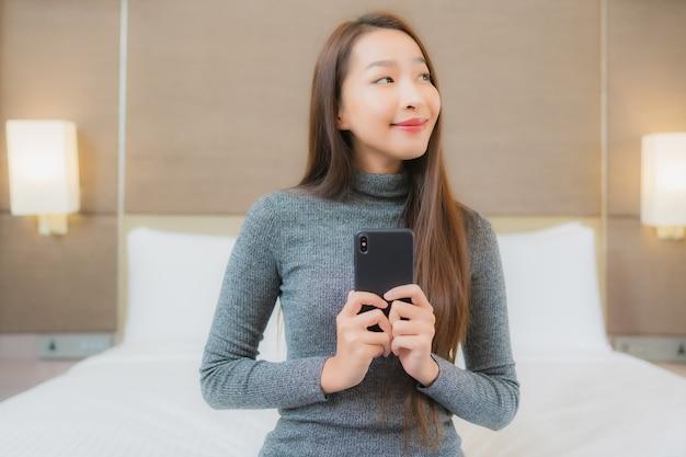 Porträt der schönen jungen asiatischen frau, die smartphone im schlafzimmer hält