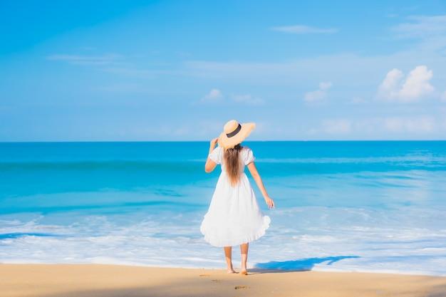 Porträt der schönen jungen asiatischen frau, die um strand mit weißen wolken auf blauem himmel im reiseurlaub entspannt