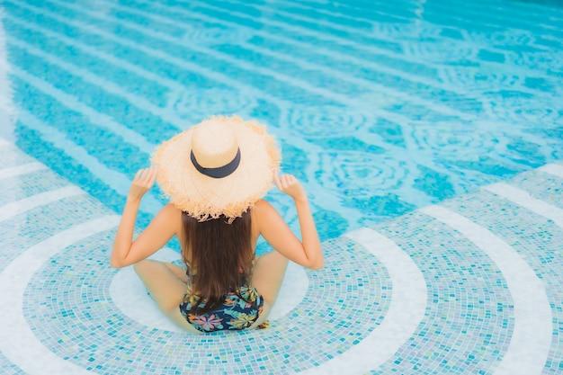 Porträt der schönen jungen asiatischen frau entspannt auf dem swimmingpool im hotelresort