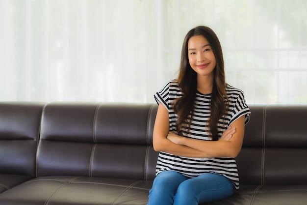 Porträt der schönen jungen asiatischen frau entspannt sich auf sofa im wohnzimmer