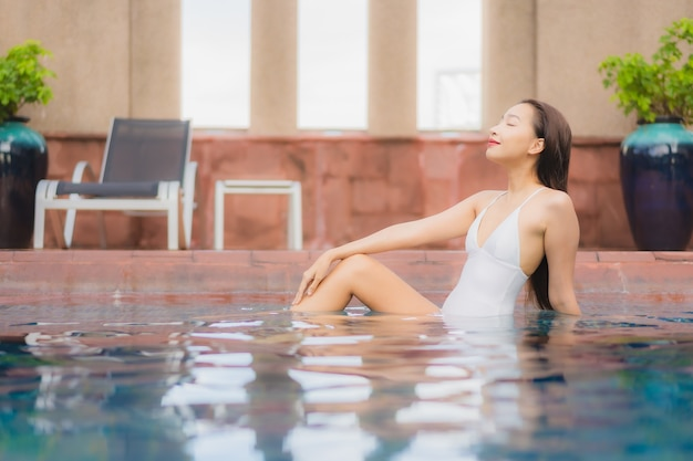 Porträt der schönen jungen asiatischen frau entspannt sich im pool