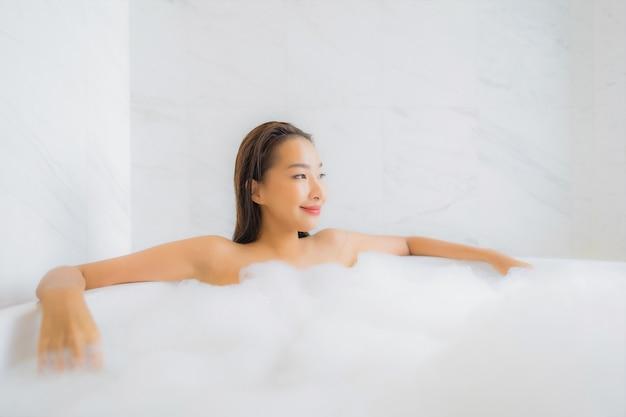 Porträt der schönen jungen asiatischen frau entspannt sich in der badewanne