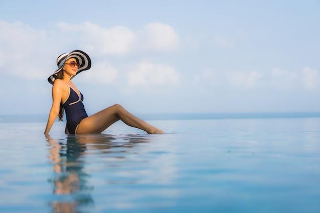 Porträt der schönen jungen asiatischen frau entspannt sich um schwimmbad im hotelresort