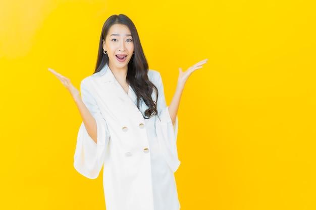 Porträt der schönen jungen asiatischen frau lächelt auf gelber wand