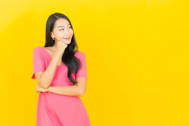 Porträt der schönen jungen asiatischen frau lächelt im rosa kleid auf gelber wand