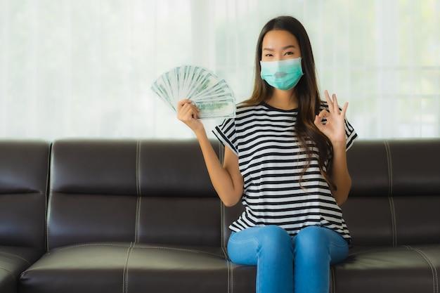 Porträt der schönen jungen asiatischen frau mit maske auf sofa, die geld zeigt