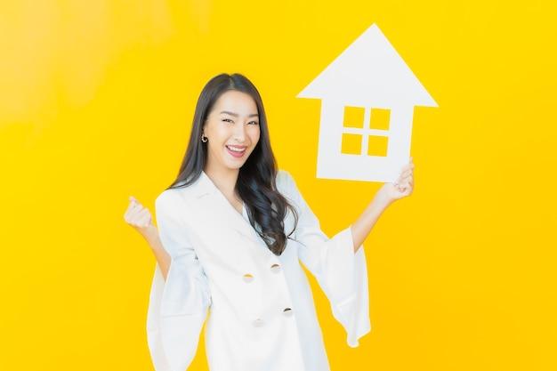 Porträt der schönen jungen asiatischen frau mit papierhaus auf gelber wand