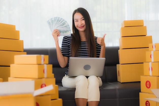Porträt der schönen jungen asiatischen frau mit papppaketboxen und geld