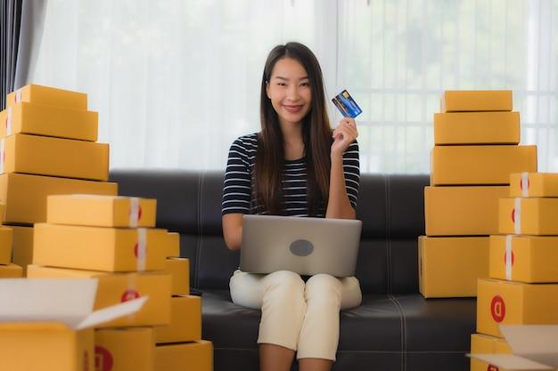 Porträt der schönen jungen asiatischen frau mit papppaketboxen und kreditkarte