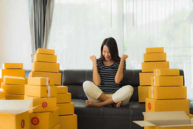 Porträt der schönen jungen asiatischen frau mit papppaketboxen