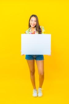 Porträt der schönen jungen asiatischen frau mit weißer leerer plakatwand auf gelber wand