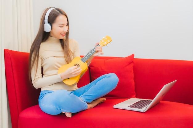 Porträt der schönen jungen asiatischen frau spielen ukulele auf sofa im wohnzimmer interieur