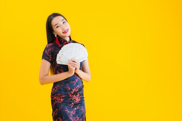 Porträt der schönen jungen asiatischen frau trägt chinesisches kleid und hält viel geld