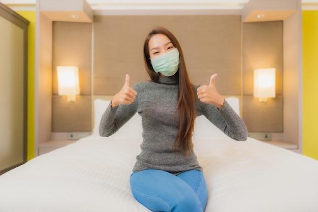 Porträt der schönen jungen asiatischen frau trägt maske im schlafzimmer