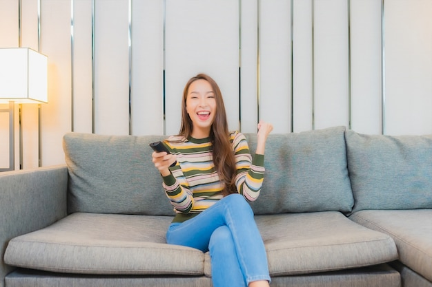 Porträt der schönen jungen asiatischen frau verwenden fernsehfernbedienung auf sofa im wohnzimmer interieur