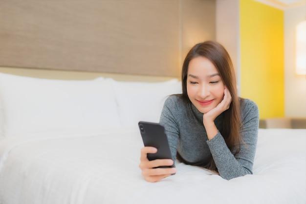 Porträt der schönen jungen asiatischen frau verwendet smartphone auf dem bett