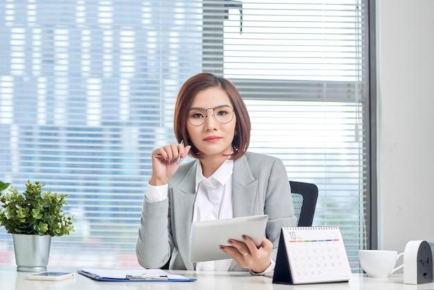 Porträt der schönen jungen asiatischen geschäftsfrau, die sitzt und eine tablette hinter dem tisch am arbeitsplatz verwendet