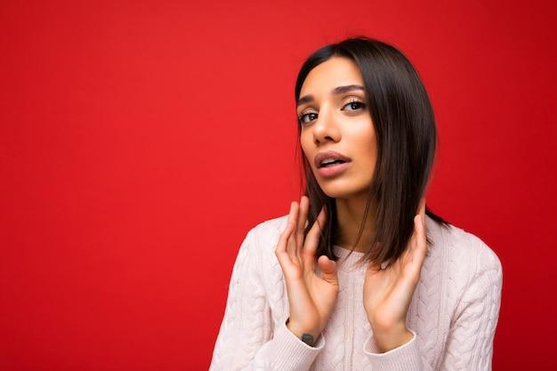 Porträt der schönen jungen brünetten frau, die gestricktes trikot trägt, einzeln auf rotem hintergrund mit freiem raum und kurzes haar berührend.