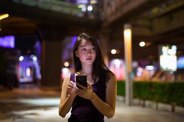 Porträt der schönen jungen chinesischen frau im freien bei nacht