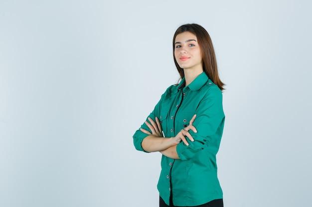 Porträt der schönen jungen dame, die arme im grünen hemd gefaltet hält und stolze vorderansicht schaut