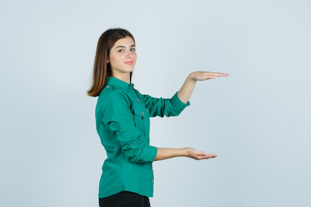 Porträt der schönen jungen dame, die großes zeichen im grünen hemd zeigt und fröhlich schaut
