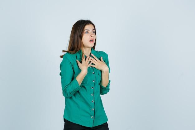 Porträt der schönen jungen dame, die hände auf brust in grünem hemd hält und schockierte vorderansicht schaut