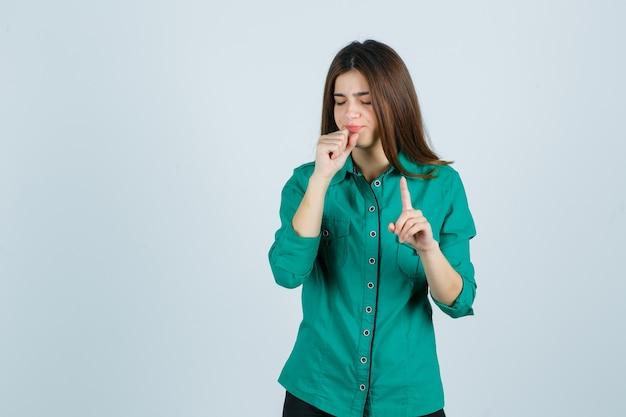 Porträt der schönen jungen dame, die halt auf einer winzigen geste zeigt, während sie im grünen hemd hustet und kranke vorderansicht schaut