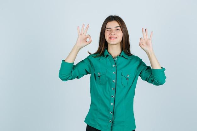 Porträt der schönen jungen dame, die ok geste zeigt, während im grünen hemd zwinkert und lustige vorderansicht schaut