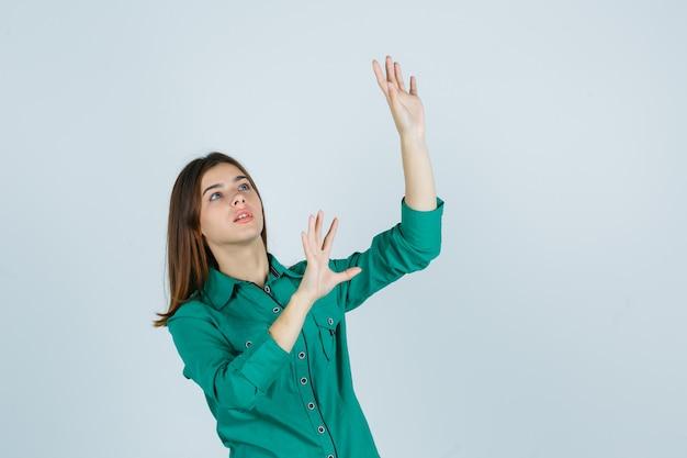 Porträt der schönen jungen dame, die stoppgeste in grünem hemd zeigt und erschreckte vorderansicht schaut