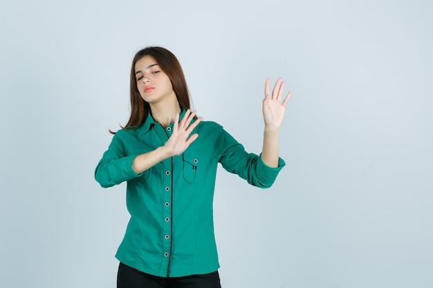 Porträt der schönen jungen dame, die stoppgeste in grünem hemd zeigt und genervte vorderansicht schaut