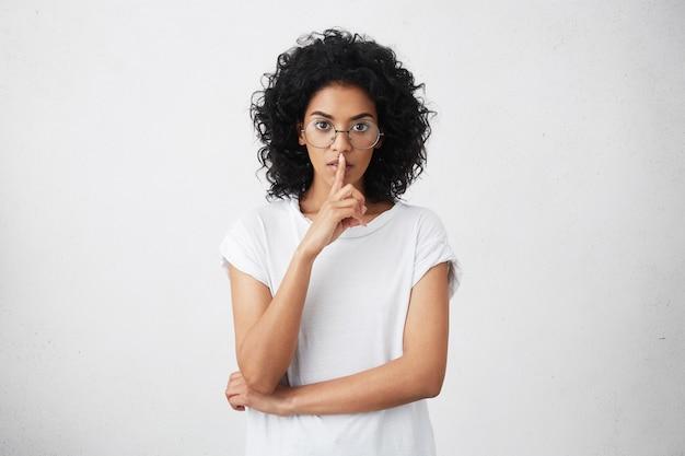Porträt der schönen jungen dunkelhäutigen mutter, die stilvolle runde brillen trägt