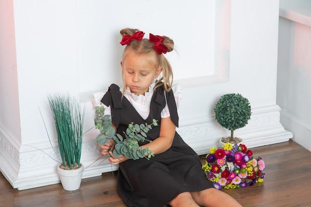 Porträt der schönen jungen erstklässlerin schulmädchen in einem weißen hemd und einem schwarzen zopf mit topfblumen in ihren händen