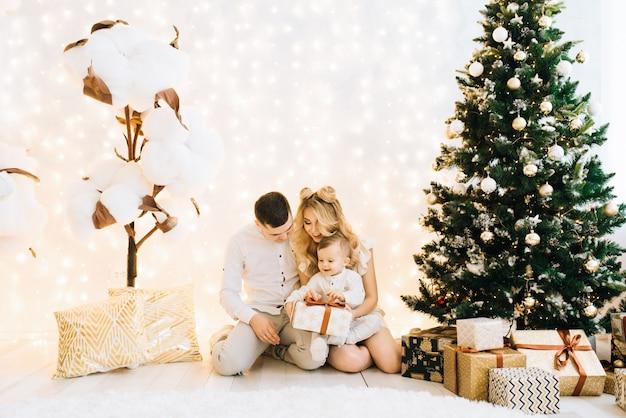 Porträt der schönen jungen familie auf weihnachtsbaum und weißer baumwolle