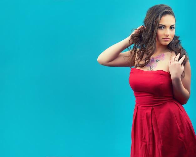 Porträt der schönen jungen frau auf dem roten weinlesekleid an der blauen wand. junges weibliches modell.
